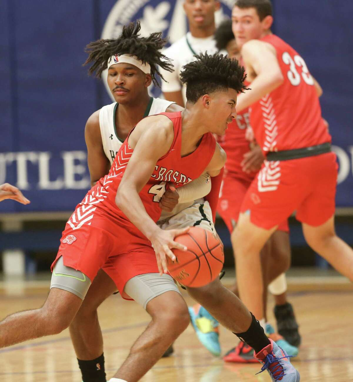 """Crosby's Sean """"PJ"""" Haggerty (4) dribbles around Hightower's Bryce Griggs (12) during playoff game action at Butler Fieldhouse in Houston on Wednesday, Feb. 24, 2021. Crosby won the game 68-54."""