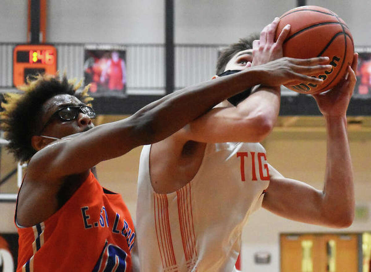 Edwardsville's Brennan Weller, right, is fouled as he goes up for a shot against East St. Louis forward Jalen Watson in the third quarter of Wednesday's game inside Lucco-Jackson Gymnasium.
