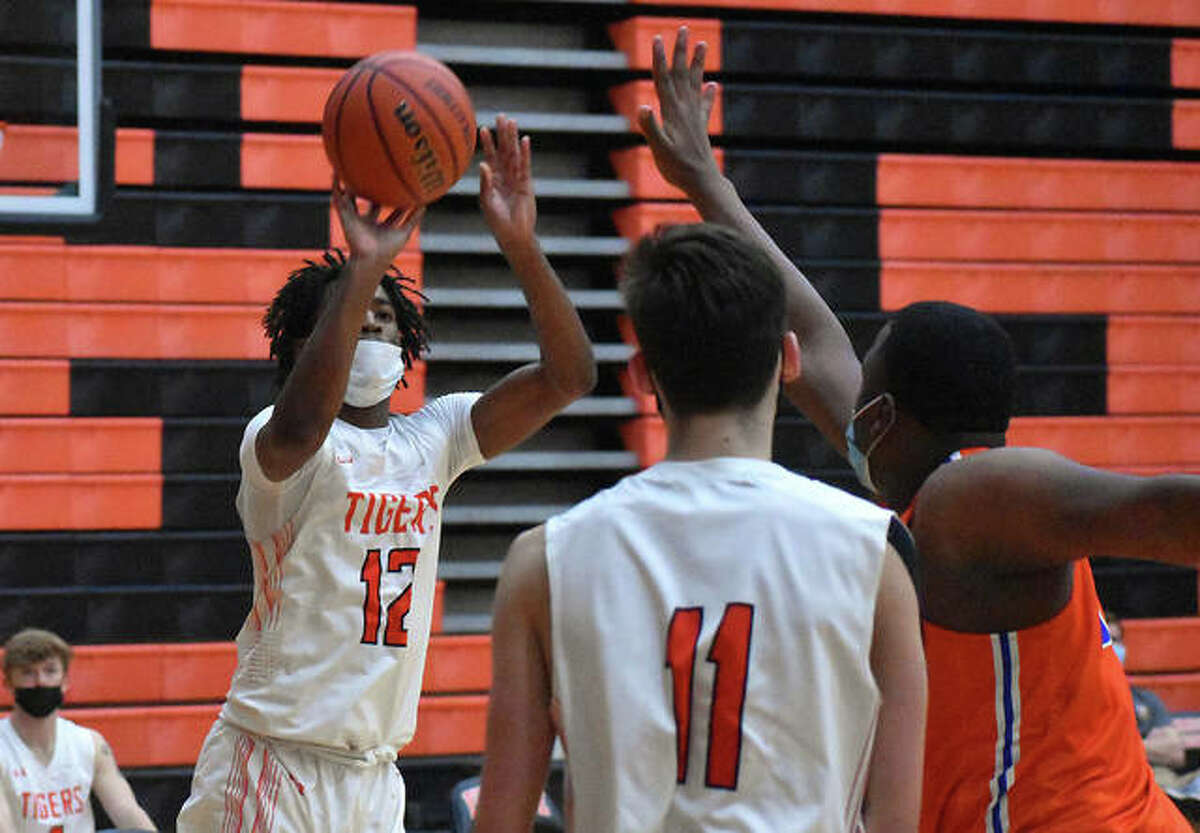 Edwardsville's Gabe James, left, puts up a 3-point shot in the third quarter of Wednesday's game against East St. Louis.