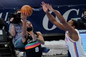 Spurs guard Patty Mills (8) shoots in front of Oklahoma City Thunder center Al Horford during the second half Wednesday, Feb. 24, 2021, in Oklahoma City.