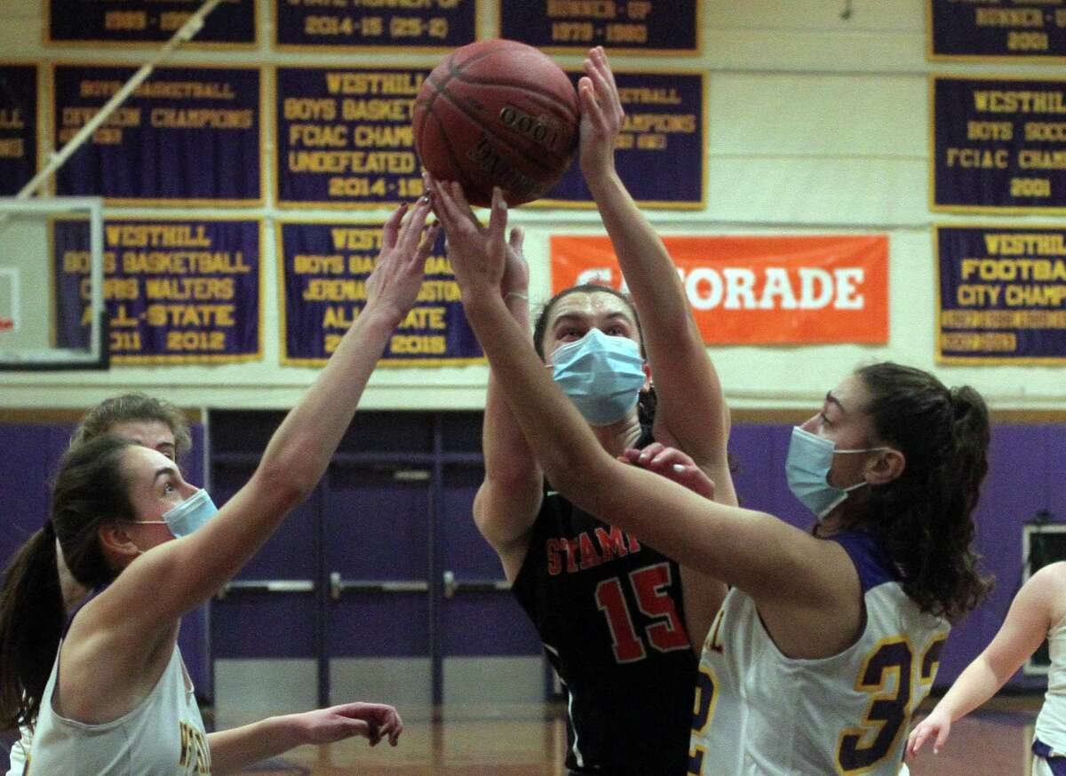 Stamford's Samantha Albert (15) looks for two points as Westhill's Olivia Conte (14), left, and Paige Hochadel (32) defend during girls basketball action in Stamford, Conn., on Saturday Feb. 20, 2021.