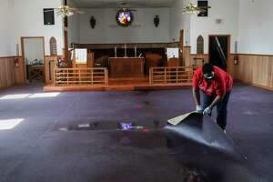 Pastor Enid Henderson rolls up wet carpet as she and others clean up water from a busted pipe Saturday, Feb. 20, 2021, at Ebenezer United Methodist Church in Houston.
