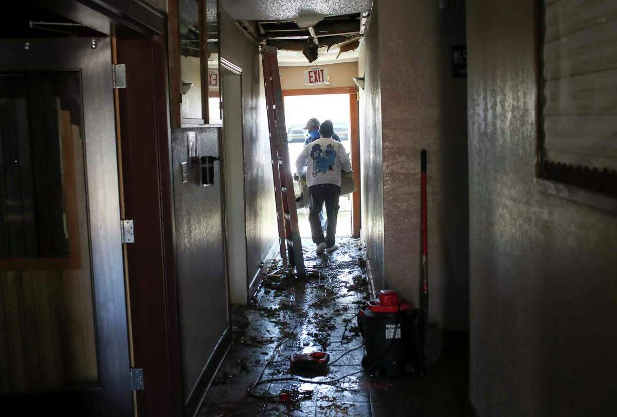 Jason Sparks, front, and Gary Collins carry out wet carpet as they clean up, after a pipe busted during the winter storms, Saturday, Feb. 20, 2021, at Ebenezer United Methodist Church in Houston.