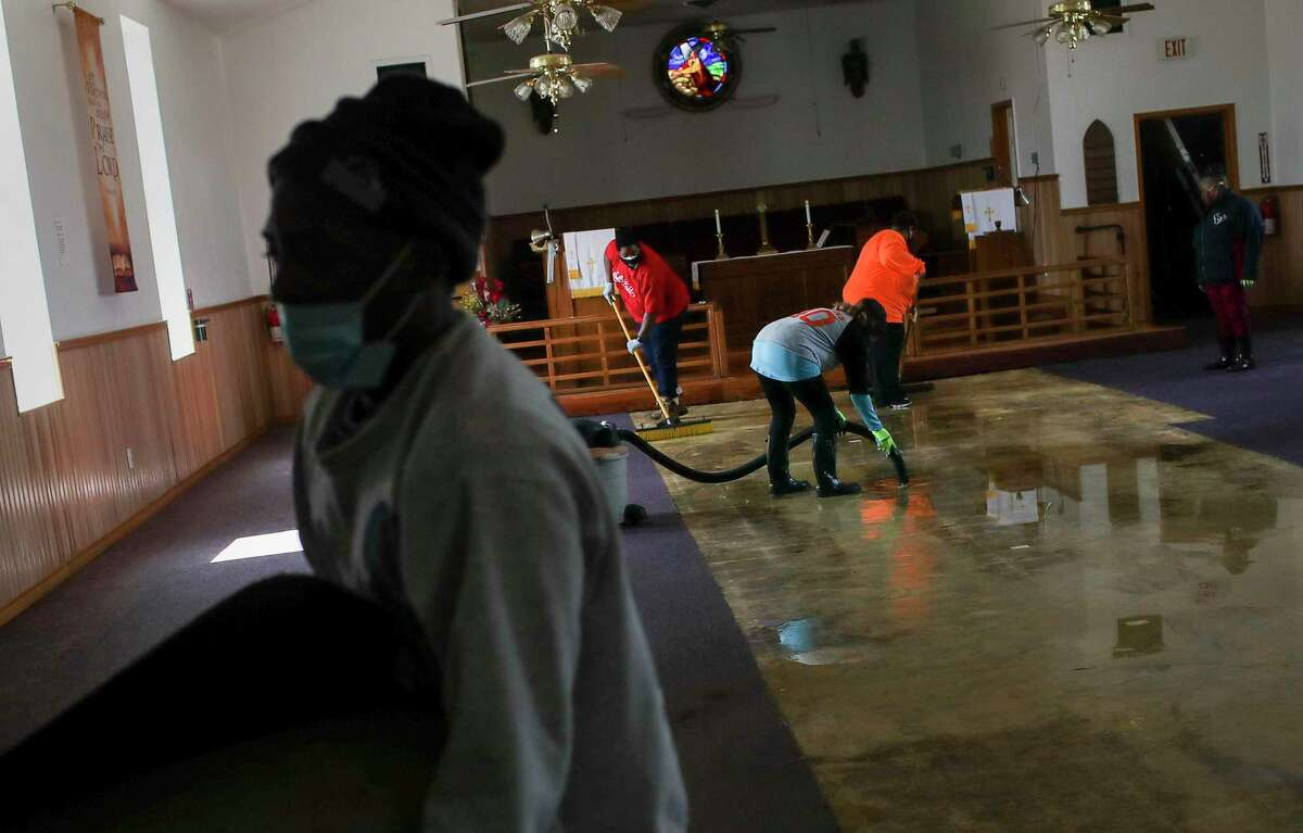 People clean up water from a busted pipe Saturday, Feb. 20, 2021, at Ebenezer United Methodist Church in Houston.