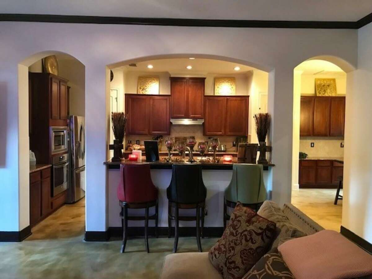 Before: Arched doorways, a pass-through wall and dark finishes made the kitchen feel separate and dated.