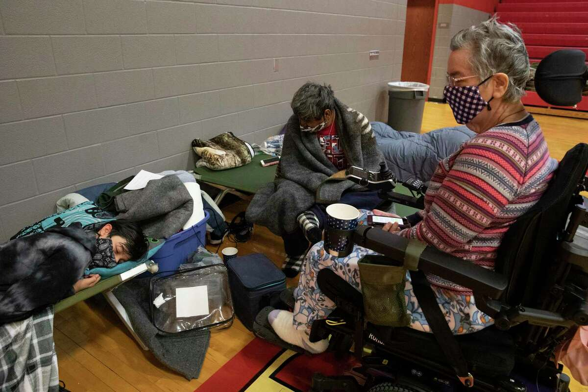 Edward De La Cruz sits on a cot with a blanket next to his wife Lisa and his son Joesph at an emergency warming shelter set up at Judson High School in Converse on Feb. 17, 2021. The family had been without electricity since early Feb, 15.