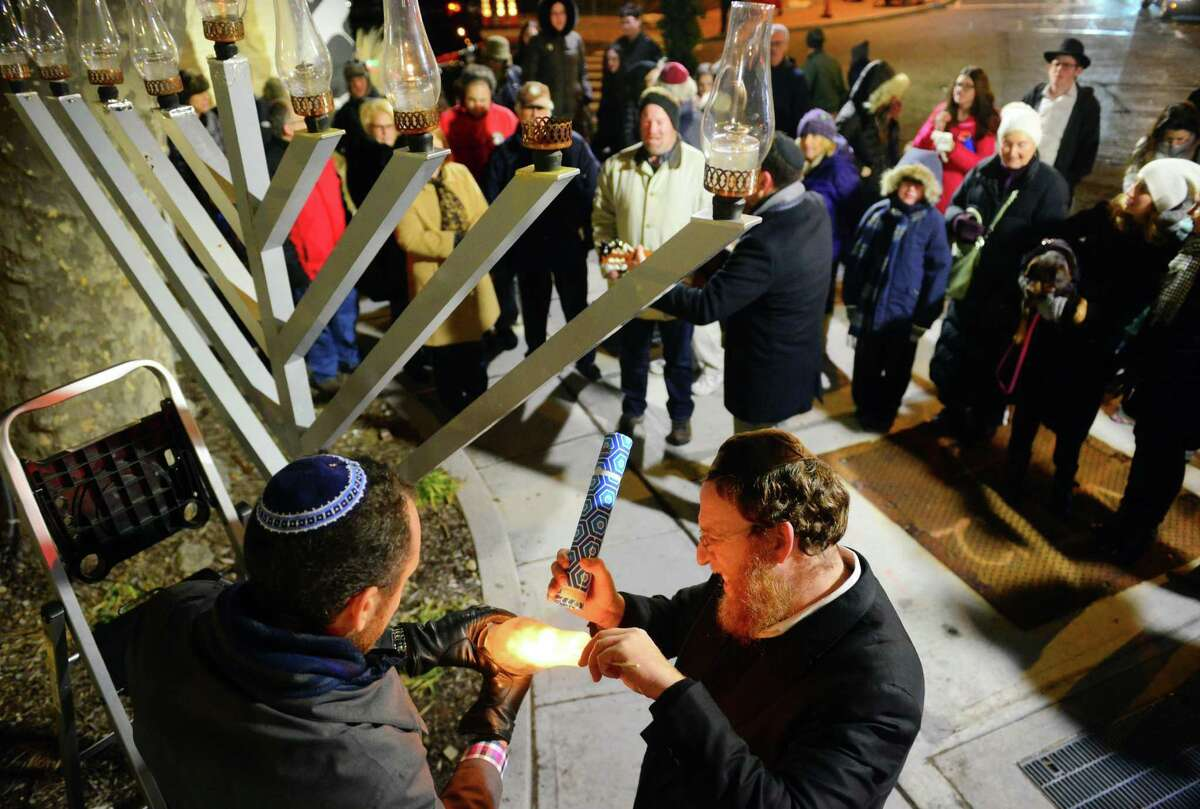 Rabbi Yehuda Kantor, right, helps Rabbi Michael Friedman light the Menorah candle for the last day of Hanukkah during the 23rd First Night Westport 2017 New Year's Eve celebration in Westport on Dec. 31, 2016.