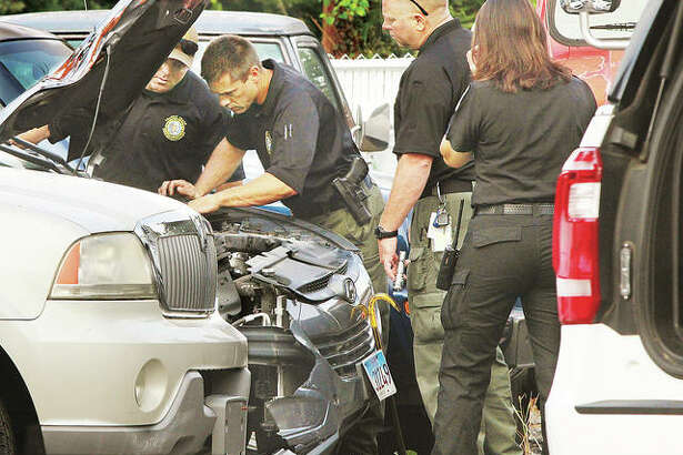 In this September photo, Alton Police Sgt. Emily Hejna joins the Illinois State Police and members of the Metro East Crash Assistance Team examining a Hyundai Tucson involved in a fatal motorcycle crash in Alton. State officials report Illinois traffic deaths rose in 2020 despite reports of fewer people on roads.