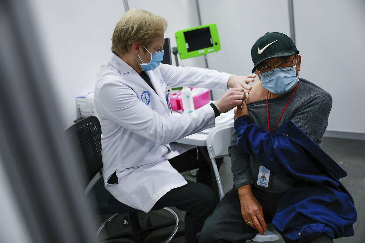 Antonio Rabanal, 73, right, gets vaccinated at the Moscone Center vaccination site by RN Scott Keech, left, on Friday, Feb. 12, 2021 in San Francisco, Calif. San Francisco is the latest California city to temporarily shutter a mass vaccination site due to lack of vaccine, joining Los Angeles in pausing inoculations amid a national shortage. Officials said mass vaccinations are on hold at Moscone convention center for one week until supply ramps up. On Tuesday, Feb. 16, 2021, two new mass vaccination sites with doses from the federal government will open in Oakland and in Los Angeles. (Gabrielle Lurie/San Francisco Chronicle via AP)