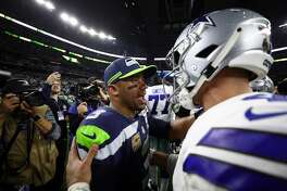 Dak Prescott of the Dallas Cowboys talks with Russell Wilson of the Seattle Seahawks after the Cowboys defeated the Seahawks 24-22 in the Wild Card Round at AT&T Stadium on January 05, 2019 in Arlington, Texas. (Photo by Ronald Martinez/Getty Images)