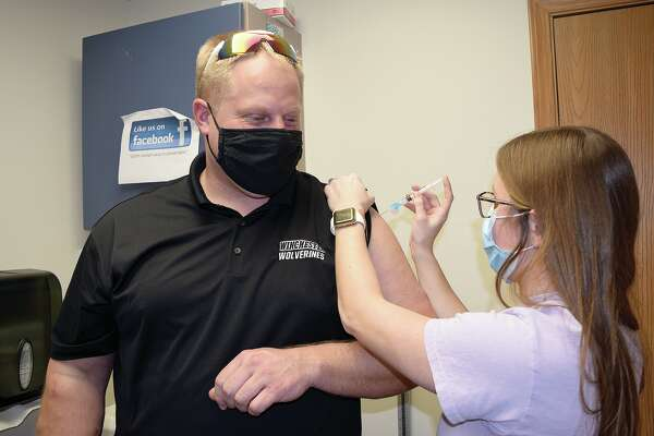 Scott County Health Department nurse Meghan VanDeVelde gives Winchester Grade School Principal Andy Stumpf a COVID-19 vaccination.