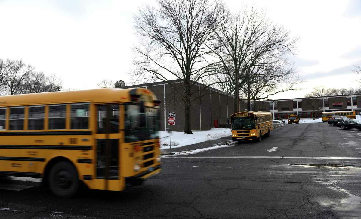 Buses drop off students at Turn of River Middle School in Stamford, Conn. Tuesday, Feb. 23, 2021. Turn of River is one of three schools recently chosen for air improvement projects to be funded by federal COVID-19 relief dollars.