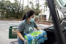 Nayely Reyes loads a case of water into the back of a vehicle during a distribution event at Interfaith, Wednesday, Feb. 24, 2021, in The Woodlands.