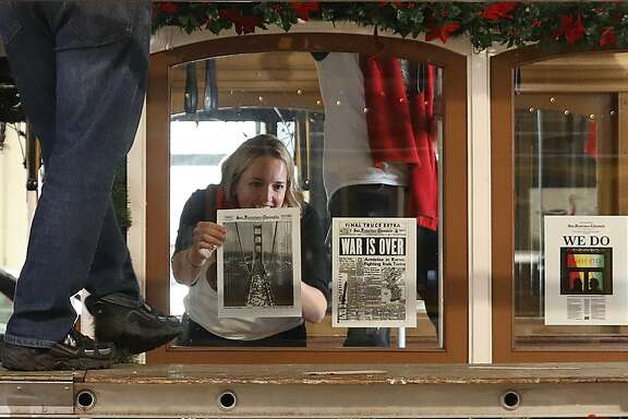Chronicle reporter Heather Knight (left) decorates a cable car with past front pages at the cable car barn on Tuesday, December 11, 2018, in San Francisco, Calif.