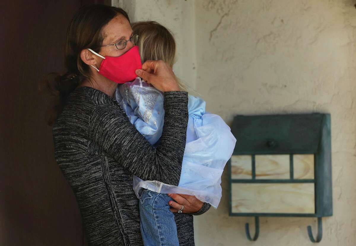 Jackie B. holds daughter Callie, 3, on the doorstep of their Moraga home. The girl was attacked by a coyote last week, one of five attacks in the past eight months.