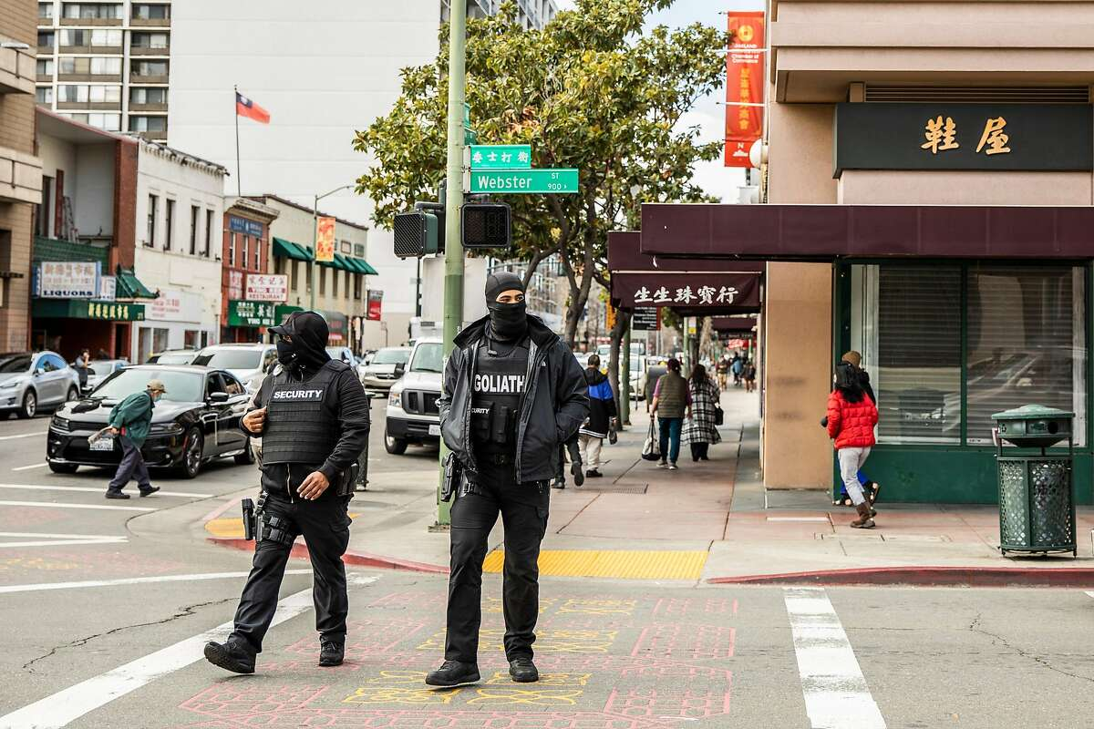 Armed security members from Goliath Protection Group, contracted and funded by a GoFundMe crowdfunding campaign, patrol on Webster Street in the Chinatown district of Oakland, California Tuesday, Feb. 16, 2021.