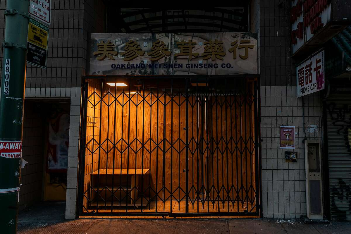 A barricaded storefront is illuminated by an incandescent light along a nearly emptied 9th Street just before sunset in the Chinatown district of Oakland, California Tuesday, Feb. 16, 2021.