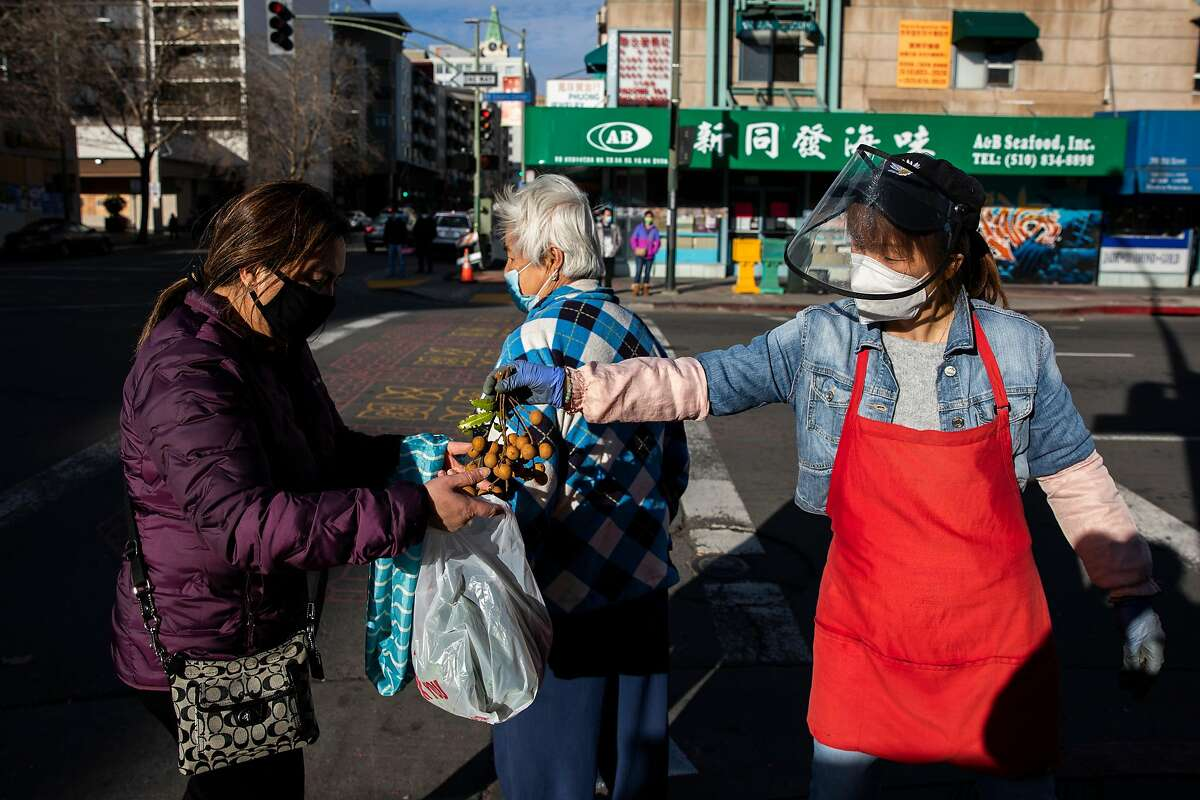 A grocery worker, right, passes a bundle of fresh longan to a woman in the Chinatown district of Oakland, California Tuesday, Feb. 16, 2021. Community members are on heightened alert after the recent increase in violent crimes, many caught on camera, toward the Asian American community throughout the Bay Area. Despite an increased police presence, armed private security, and volunteer groups patrolling the area around Oakland Chinatown, many businesses continue to worry and are taking extra precautionary measures such as boarding up storefronts and closing hours earlier despite how the pandemic-driven economic downturn has already impacted many.