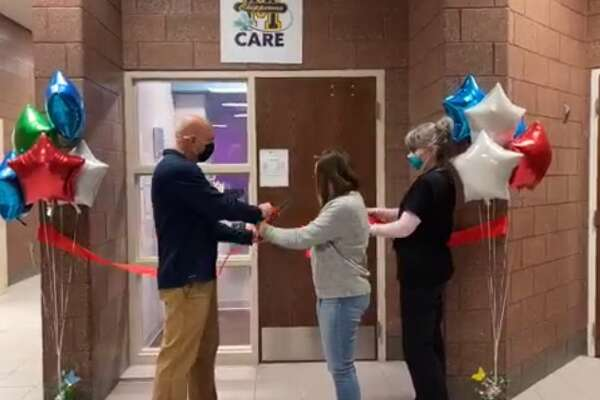 Andy Huber, Manistee Middle High School principal, and junior Lauren Bell cut the ribbon during a virtual ceremony to celebrate the opening of the Child and Adolescent Health Center on Wednesday night.