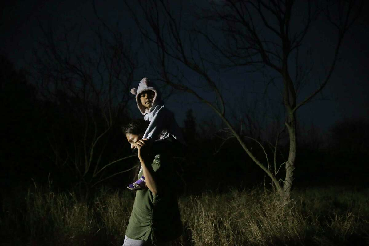 A migrant woman carries a child as they walk on a caliche road after crossing the Rio Grande into the U.S. at a placed called Rincon del Diablo, Devil's Corner, in Hidalgo County, Texas, Wednesday, Feb. 24, 2021. Over two hundred crossed a in short time at the spot where families turn themselves into immigration authorities.