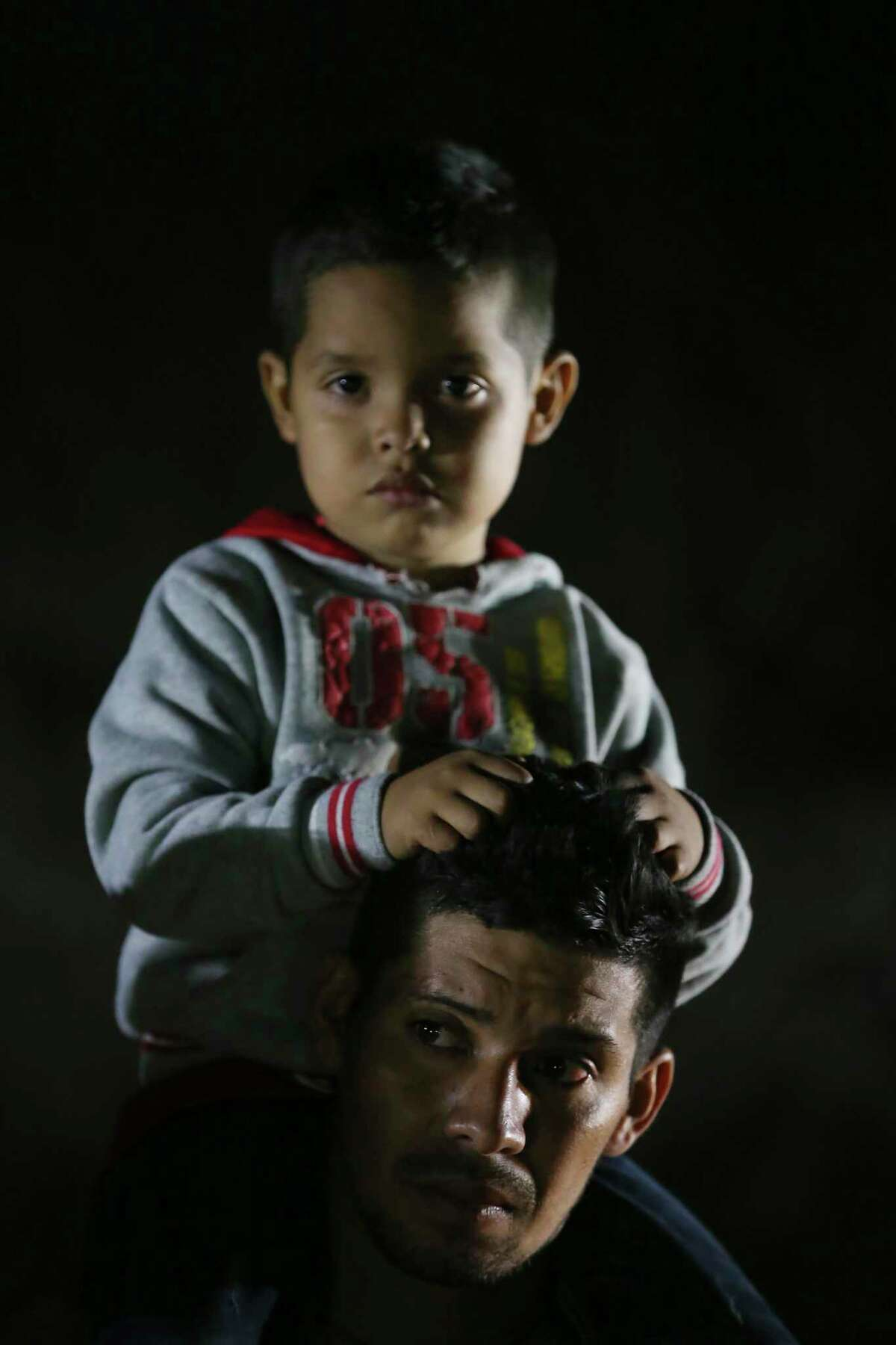 A migrant carries a child after crossing the Rio Grande into the U.S. at a placed called Rincon del Diablo, Devil's Corner, in Hidalgo County, Texas, Wednesday, Feb. 24, 2021. Over two hundred crossed a in short time at the spot where families turn themselves into immigration authorities.