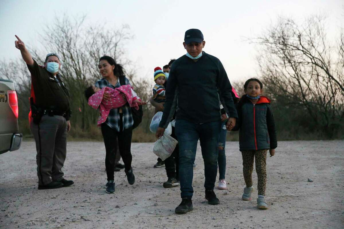 Migrant families are directed by a Hidalgo County Precinct 3 Constable Deputy to a U.S. Border Patrol processing site by Anzalduas International Bridge, Wednesday, Feb. 24, 2021. Over two hundred migrants, mostly Central Americans, crossed the Rio Grande at the Devil's Corner.