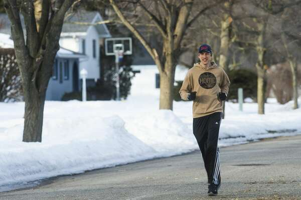 Peter Kroon of Midland goes for a run Thursday, Feb. 25, 2021 near his home. Kroon is one of two local runners who recently tackled a special goal: running along every street in the city of Midland. (Katy Kildee/kkildee@mdn.net)