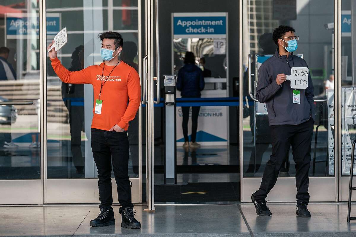 Greeters are seen holding placards with appointment times on it at the entrance to the mass vaccination site at the Moscone Center in San Francisco on Thursday, February 25, 2021. After being closed for more than a week due to a lack of available supply, the mass-vaccination site at the Moscone Center re-opened on Thursday.