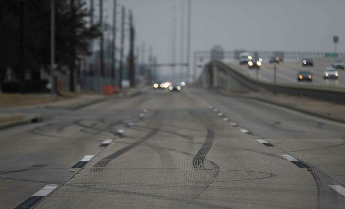 Tire marks are seen on the feeder road at the site of a car meet held Sunday, where authorities said a street takeover happened and a crash resulted in the deaths of three people. The site was photographed Thursday, Feb. 25, 2021, in Houston.