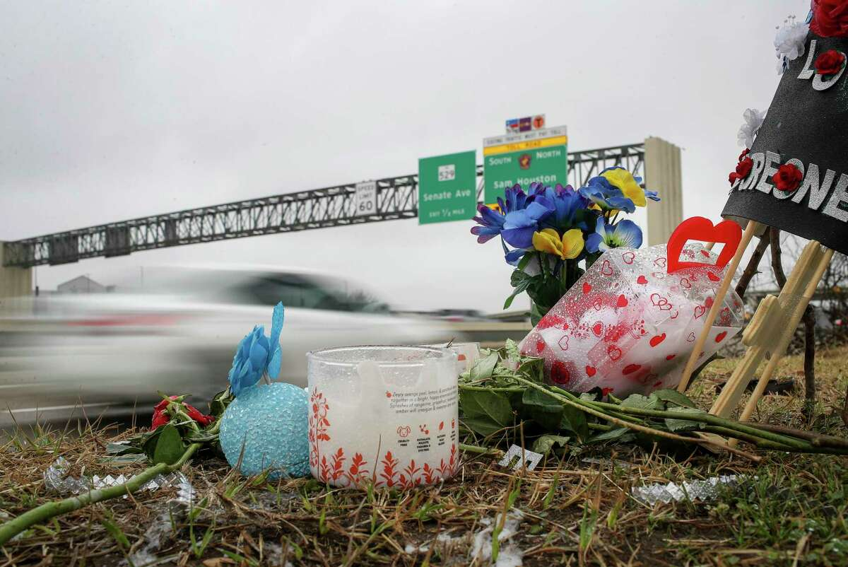 Traffic passes by a memorial at the site of a car meet held Sunday, where authorities said a street takeover happened and a crash resulted in the deaths of three people. The site was photographed Thursday, Feb. 25, 2021, in Houston.