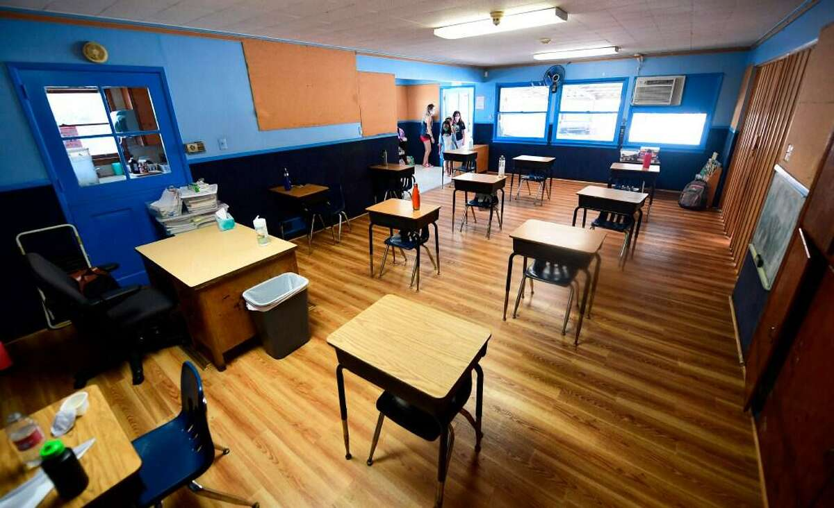 In this file photo taken on July 9, 2020 cildren in an elementary school class wearing masks enter the classroom with desks spaced apart as per coronavirus guidelines during summer school sessions in Monterey Park, California.