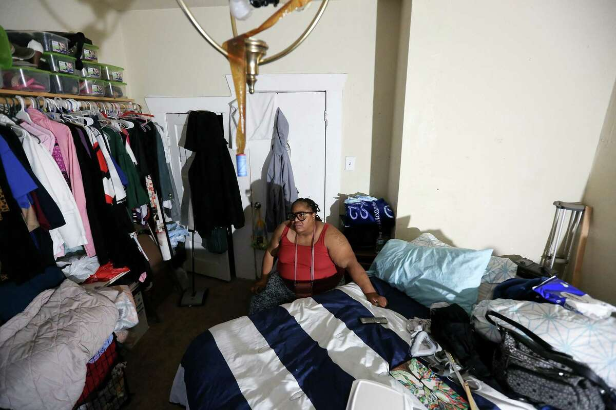 Lit by a bed-side light, Shonza Branch, 56, sits in her bedroom in her Houston on Thursday, Feb. 25, 2021. Branch spends most of her time inside bedroom since her home was heavily damaged during Hurricane Harvey and lost water in last week's storm.