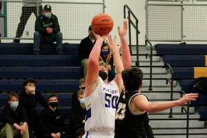 With a man in his face, Adam Domres puts up a jumper from the wing. (Robert Myers News Advocate)