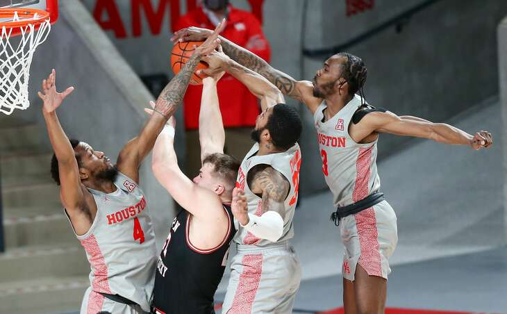 Western Kentucky Hilltoppers forward Carson Williams (22) faces Houston Cougars forwards Justin Gorham (4), Reggie Chaney (32) and guard DeJon Jarreau (3) as he tries to make a layup in the first half of game action at the Fertitta Center in Houston on Thursday, Feb. 25, 2021.