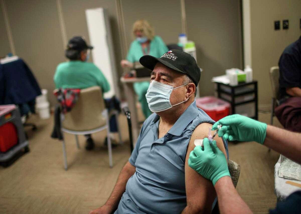 Manuel Gaitan, a Vietnam veteran, gets a vaccine shot from Michael Clark, a nurse, on Feb. 20, 2021, at Michael E. DeBakey VA Medical Center in Houston.