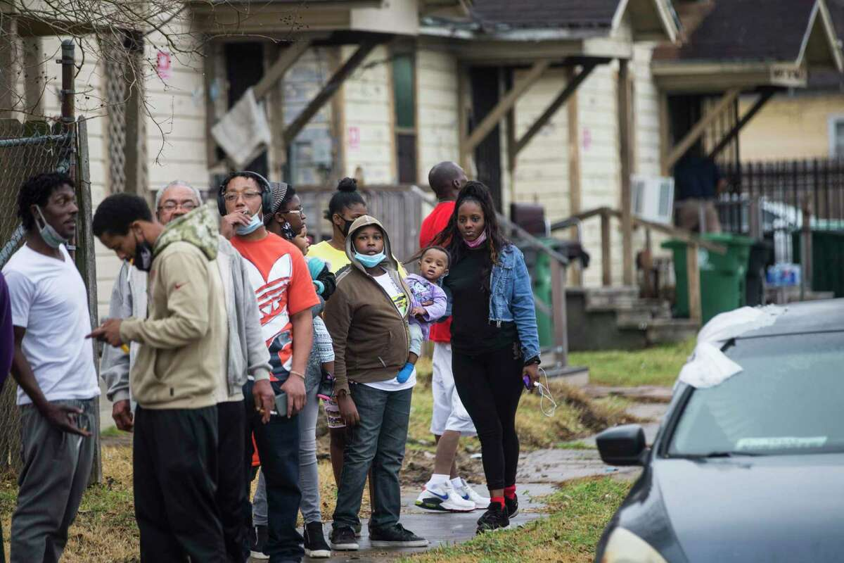 People line up for food and water in the 1900 block of Benson Thursday, Feb. 25, 2021 in Houston. Residents in the Fifth Ward neighborhood received several cases of water and food to help with recovery from the recent winter storms. The residents of the neighborhood have been without water for several days because of broken pipes from the freeze.