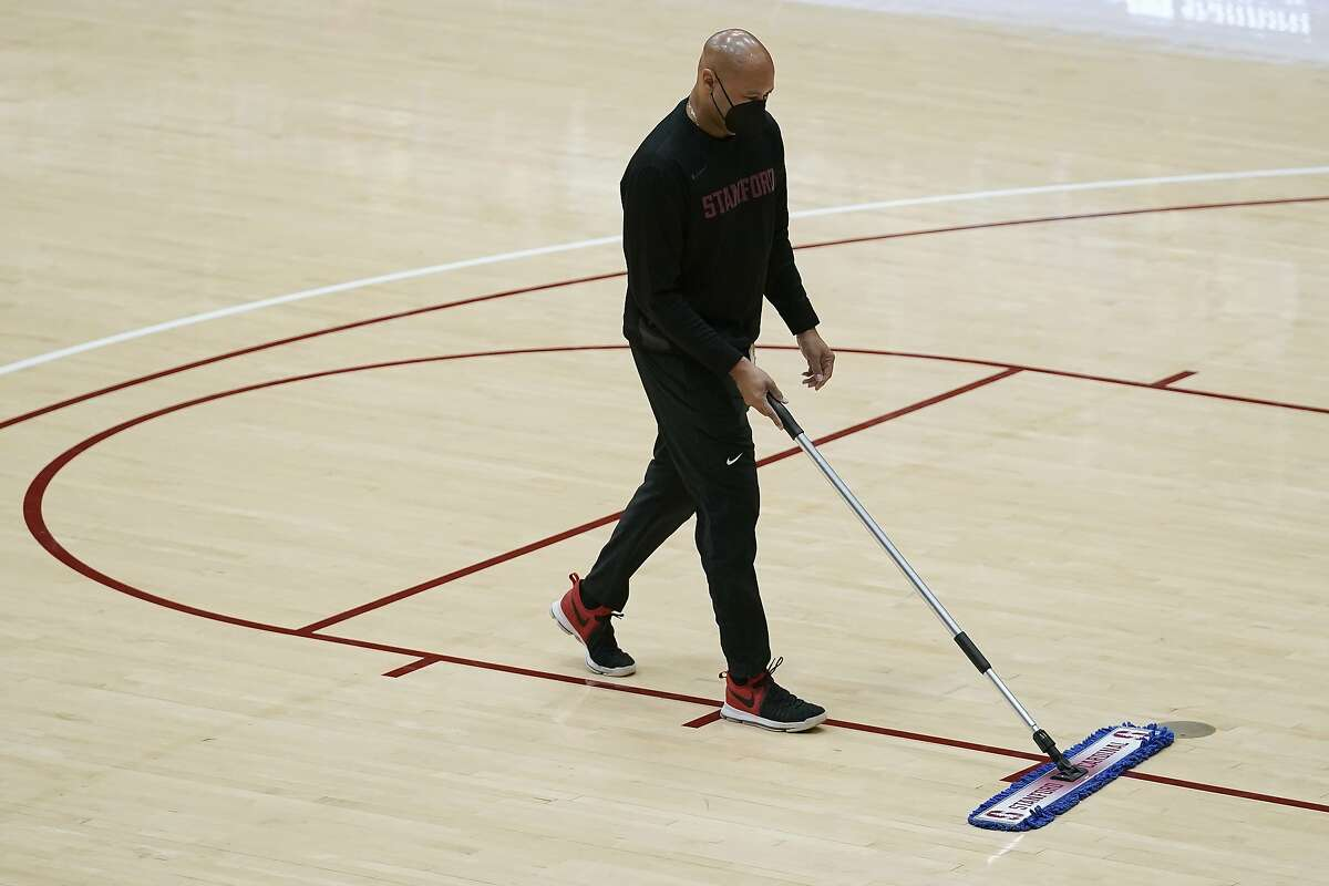 Stanford football coach David Shaw sweeps the floor during halftime of an NCAA college basketball game between Stanford and Oregon in Stanford, Calif., Thursday, Feb. 25, 2021. (AP Photo/Jeff Chiu)