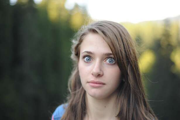 Young woman with big blue eyes staring with a shocked expression.