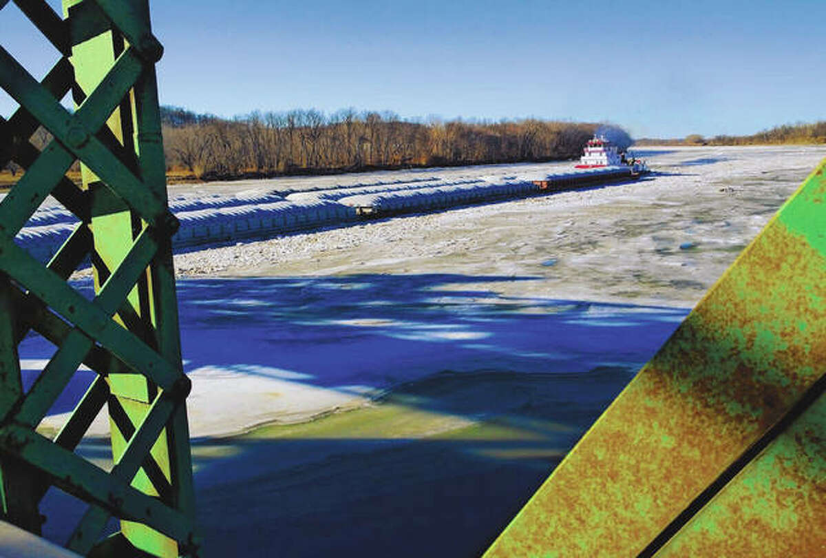 A barge captain threads the needle of the raised middle portion of the Florence Bridge earlier this week to travel through the icy river.