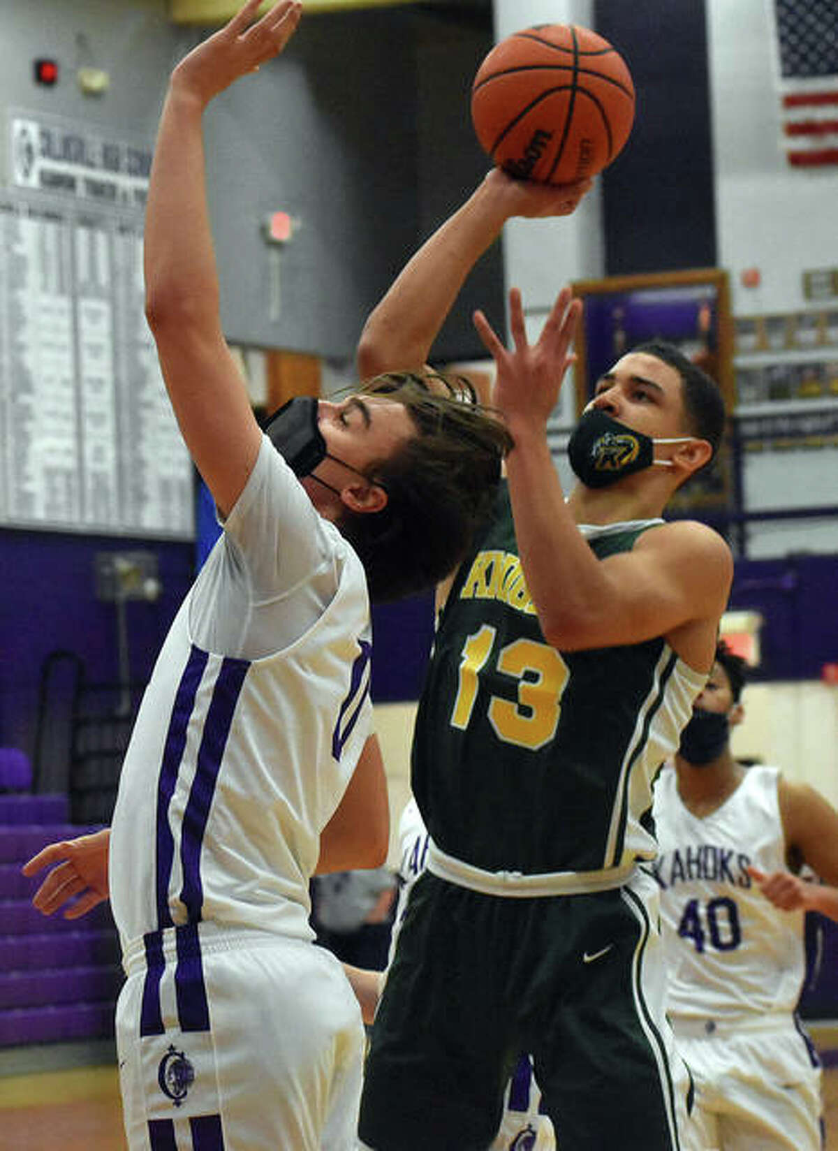Metro-East Lutheran senior AJ Smith, right, puts up a shot over Collinsville's Nate Hall during a game earlier this season inside Vergil Fletcher Gymnasium in Collinsville.