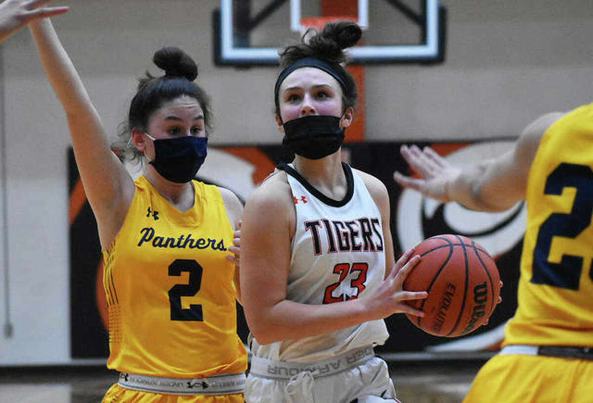 Edwardsville's Macy Silvey (23) pulls up for a jumper at the foul line between two O'Fallon defenders during Thursday's SWC girls basketball game at Lucco-Jackson Gym in Edwardsville.