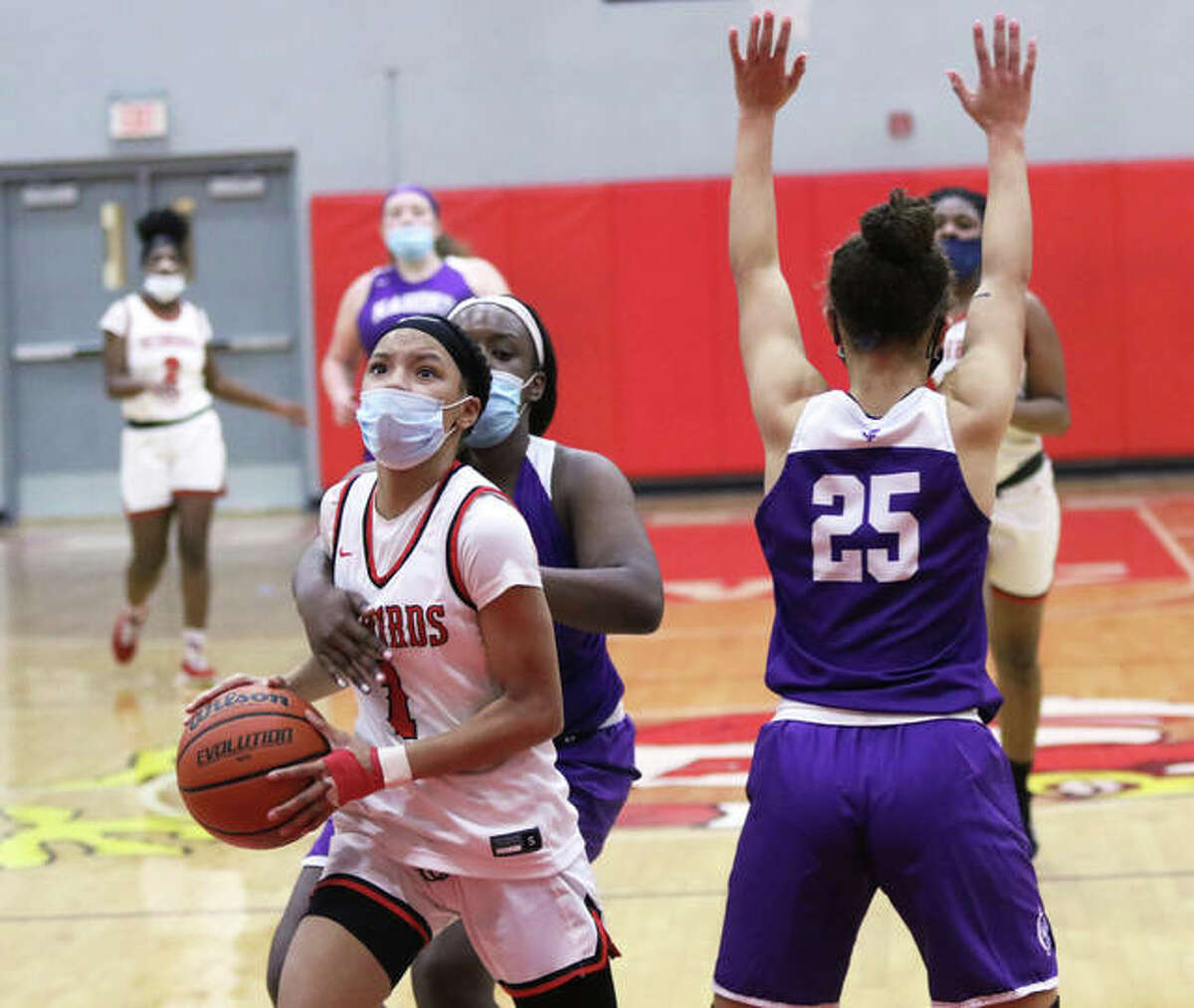 Alton's Khaliyah Goree (1) slips past Collinsville's Jordan Gary (25) and Astacia Bush in a SWC game Tuesday at Alton High in Godfrey. On Thursday, Goree scored 15 points in the Redbirds' SWC victory over East St. Louis.