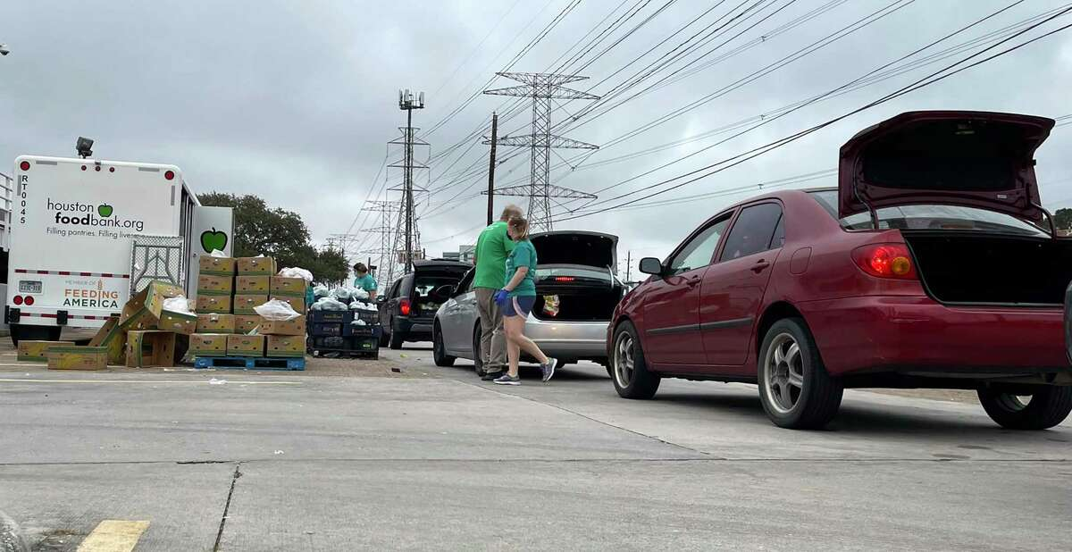 Cars line up outside Lone Star College-Houston North to take meals provided by the Houston Food Bank. The college partners with the food bank and the Aldine-Greenspoint YMCA to provide meals to its families in need.