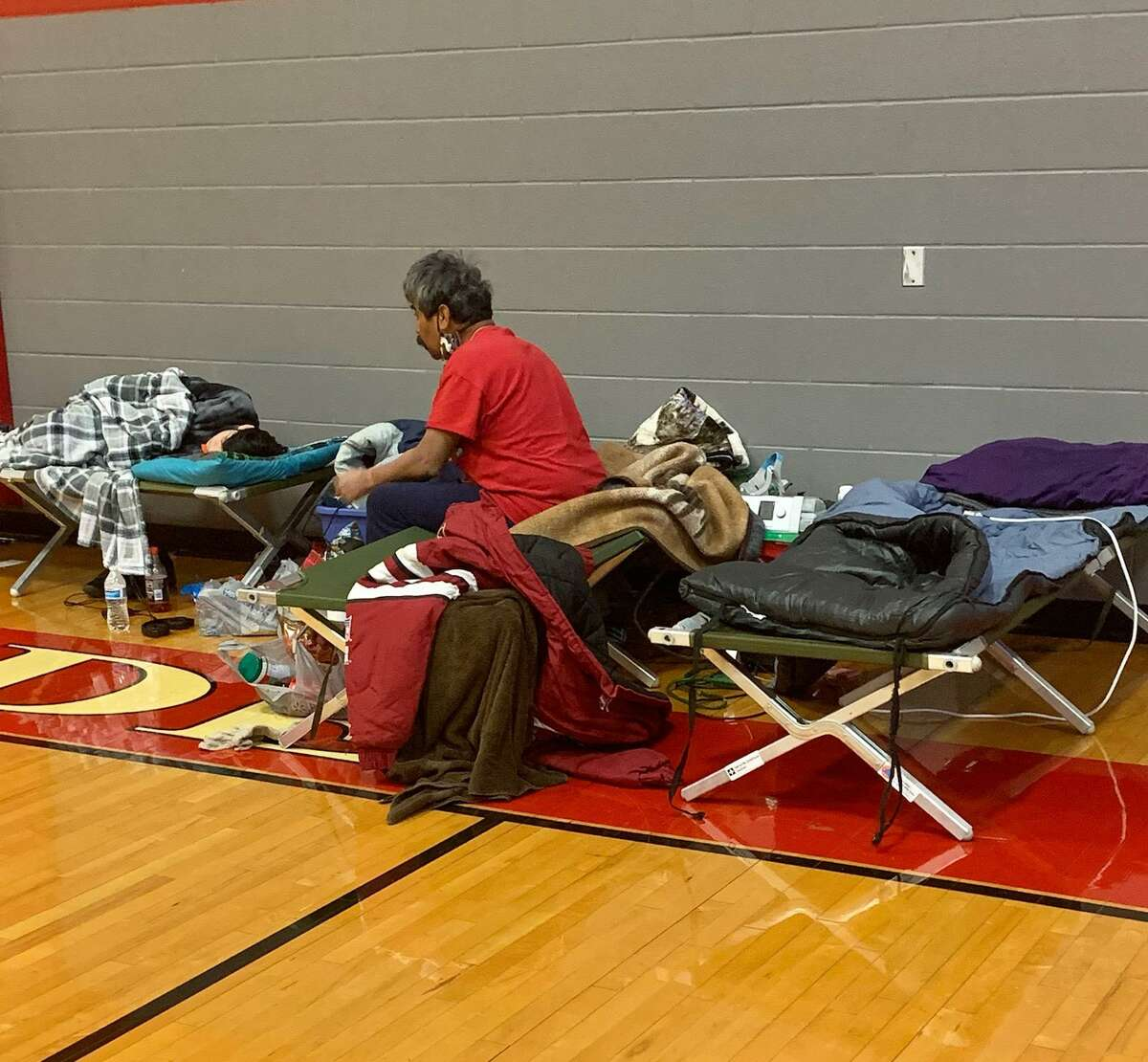 A Converse-area resident sits in the Converse-Judson ISD jointly sponsored warming center at Judson High School on Feb. 18, gathering supplies to take a shower while another person sleeps nearby.