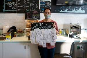 "Carrie Lee Bunblasky, owner of Tasty Waves in New Milford, holding up the ""community kindness board,"" which are receipts for items that others have bought to enable their neighbors to get a free item."