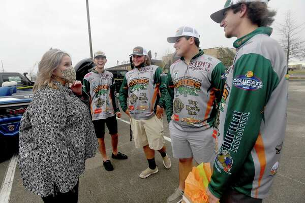From left, annglers Jack Tindel, Brett Fregia, Grady Doucet and Trent Buccholz joke with Dr. Wendy Elmore as she hands them a gift and well wishes from their proud college staff during a spirited send-off for Lamar State College Orange's fishing teams as they head to the national championship Thursday. Photo made Thursday, February 25, 2021 Kim Brent/The Enterprise