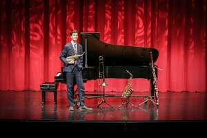 Evan Trotter-Wright is pictured with five of the instruments that he plays: the piano behind him, the soprano saxophone in his hand, and (from left), the trombone, alto saxophone, and bassoon.