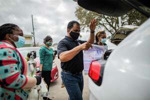 Fort Bend County Judge KP George places a bag of personal protective equipment to the vehicle of someone who came to a food distribution event at the North Richmond Neighborhood Resource Center, Wednesday, Feb. 24, 2021, in Richmond.