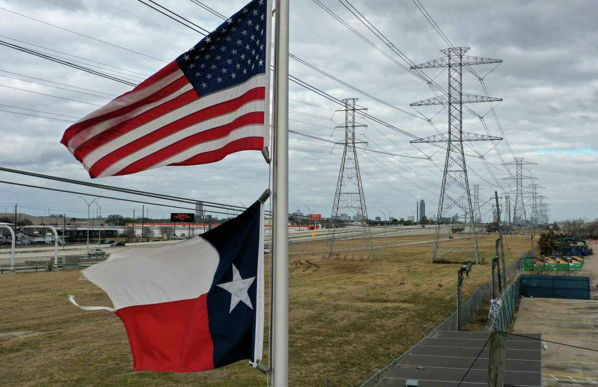 The U.S. and Texas flags fly in front of high voltage transmission towers on Feb. 21, in Houston. Millions of Texans lost power when winter storm Uri hit the state and knocked out coal, natural gas, and nuclear plants that were unprepared for the freezing temperatures brought on by the storm.