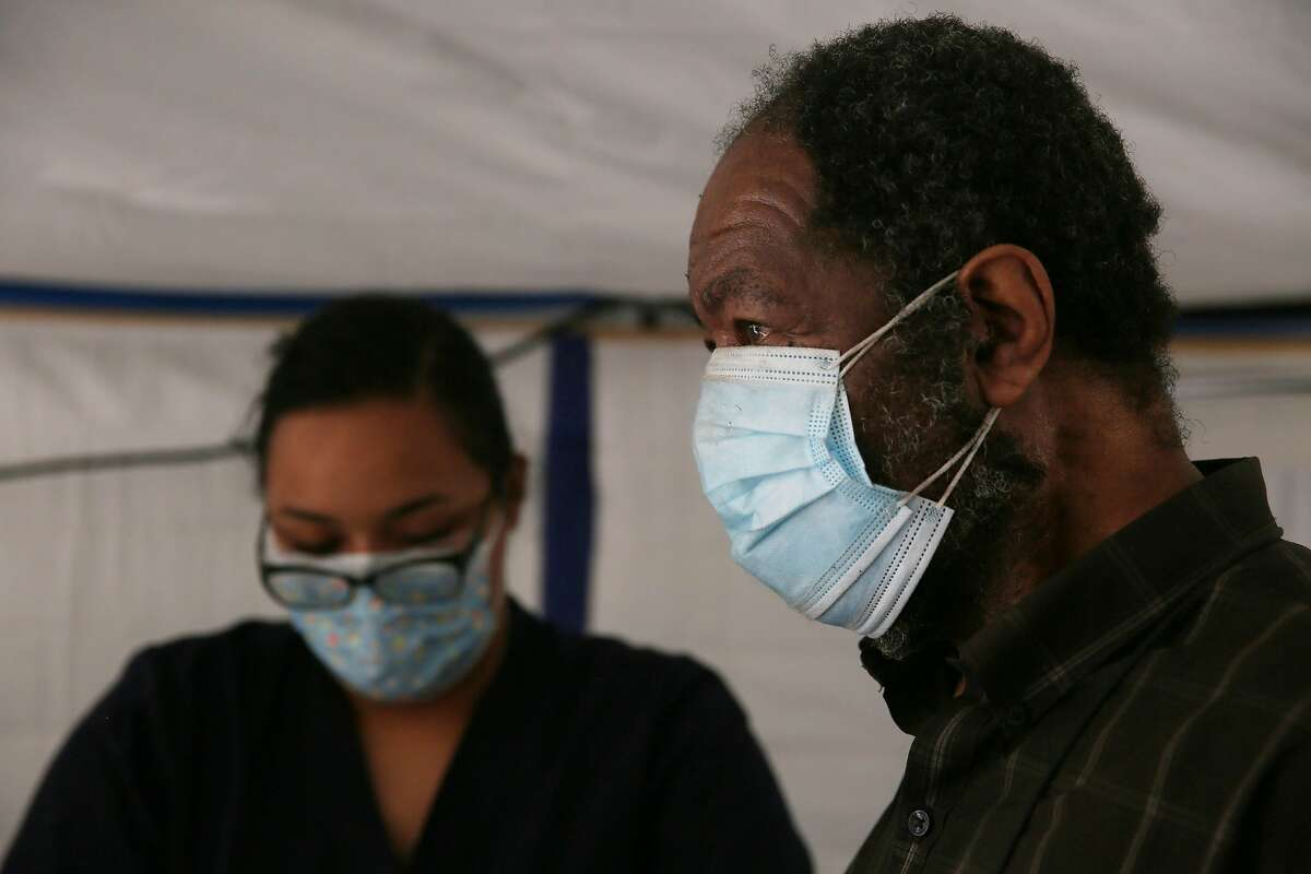 Richard Herron (right) wears a double mask while Laray Bonilla, paramedic intern City College of San Francisco, prepares a Moderna COVID-19 vaccine for him at the Southeast Health Center in San Francisco.
